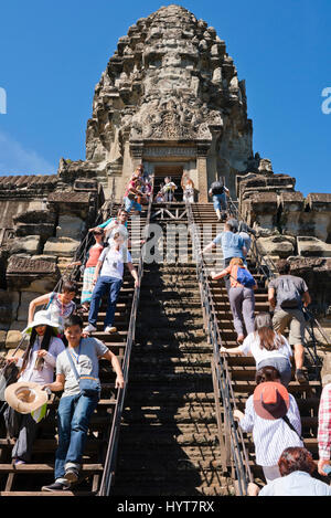 Vertical view of people visiting the main spire at Angkor Wat in Cambodia. - Stock Photo