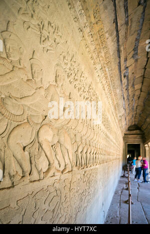 Vertical view of intricate carvings on the walls of Angkor Wat in Cambodia. - Stock Photo