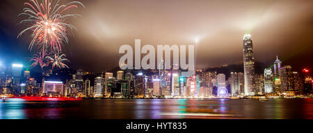Panorama view of Hong Kong skyline with lasers, floodlights and fireworks illuminating the night skies on Victoria - Stock Photo