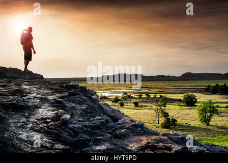Lone figure watches the sunset from Ubirr rock looking down at the Nadab floodplains. Northern Territory, Australia - Stock Photo