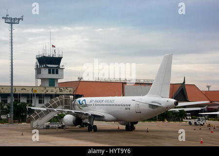 Horizontal view of a plane at a stand at Siem Reap International Airport in Cambodia. - Stock Photo