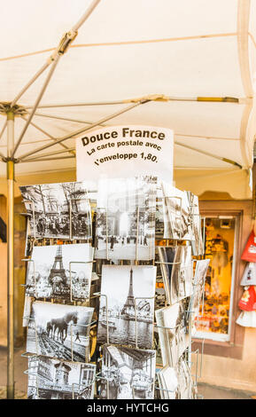 historic black and white picture postcards in a stand showing the eiffel tower and historic scenes of french everyday - Stock Photo