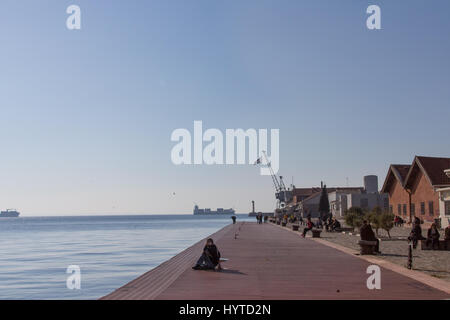 THESSALONIKI, GREECE - DECEMBER 25, 2015: People relaxing on the quay - pier of the old port of Thessaloniki, a - Stock Photo