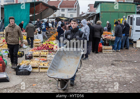 GJILAN - GNJILANE, KOSOVO - JANUARY 02, 2016: Young men selling fruits and vegetables in the local fresh market - Stock Photo