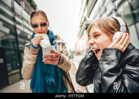 Daughter listening music on headphones with mother standing beside eating and using smart phone - Stock Photo