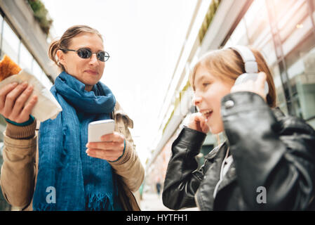 Daughter listening music on headphones with mother standing beside and eating - Stock Photo