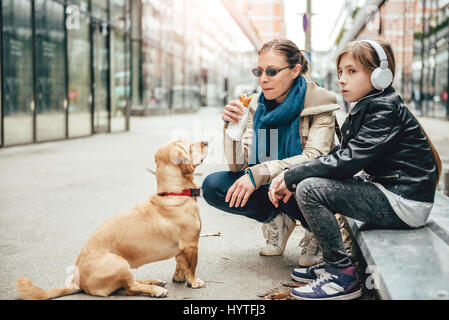 Mother eating sandwich and looking at a dog while daughter listening to music on the street - Stock Photo