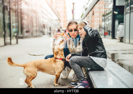 Mother eating sandwich and petting a dog while daughter listening to music on the street - Stock Photo