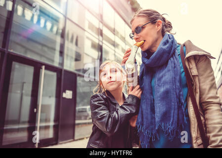 Mother and daughter walking down the city streets and eating sandwich - Stock Photo