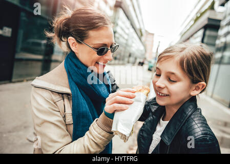 Mother walking down the city and daughter sharing sandwich - Stock Photo