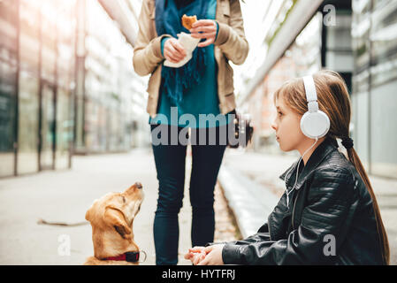 Daughter listening music on headphones while mother and her dog standing beside - Stock Photo