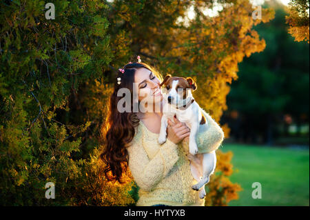 woman with a favorite dog breed Jack Russell Terrier playing in the beautiful garden - Stock Photo