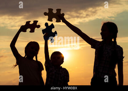 Silhouette of happy children which playing on the field at the sunset time. They having fun on the nature. Concept - Stock Photo