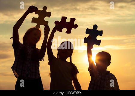Silhouette of three happy children which playing on the field at the sunset time. They having fun on the nature. - Stock Photo
