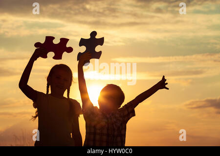 Silhouette of two happy children which playing on the field at the sunset time. They having fun on the nature. Concept - Stock Photo