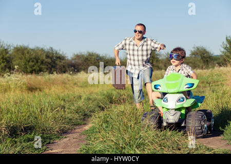 Father and son playing on the road at the day time. They driving on quad bike in the park. People having fun on - Stock Photo
