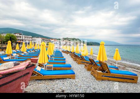Beach umbrellas and empty lounge chairs on a cloudy day. Platamonas, Pieria, Macedonia, Greece - Stock Photo