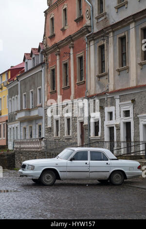 Old white Volga car parked on a cobbled side street in Kamianets-Podilskyi, Western Ukraine. The street is still - Stock Photo