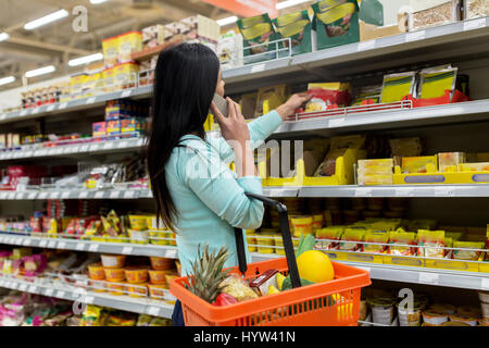 woman with food basket and smartphone at store - Stock Photo
