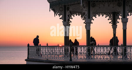1st december, 2016, Brighton, UK. People watchiong the sunset from Brighton Bandstand - Stock Photo