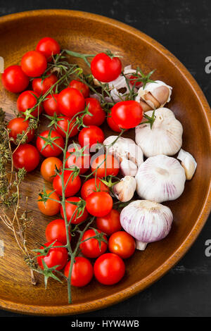 Organic cherry tomatoes with fresh garlic and thyme spices in wooden bowl - Stock Photo
