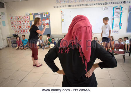 Two teachers. One Arab and one Jewish. Rinat Levi and fellow teacher Arin Ismael working with their Kindergarden - Stock Photo