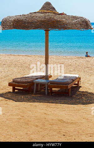 Two vacant sunbeds on a beach, in the distance a small child is playing by the sea. - Stock Photo