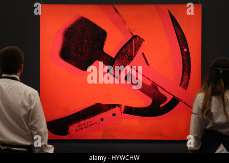 Sotheby's London, UK. 7th Apr, 2017. Members of Sotheby's staff hold Hammer and Sickle, 1976 by Andy Warhol Est - Stock Photo