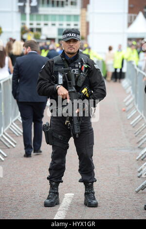 Liverpool, UK. 07th Apr, 2017. Armed Police keep an eye on guests as they arrive for Ladies Day at Aintree Racecourse, - Stock Photo