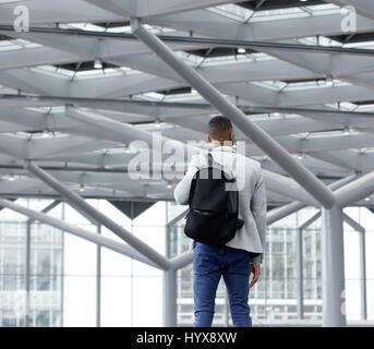 Rear view portrait of a young man standing in empty airport - Stock Photo