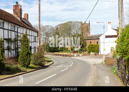 A view down Station Road showing St Luke's Church, cottage and the Red Lion public house or pub in the village of - Stock Photo