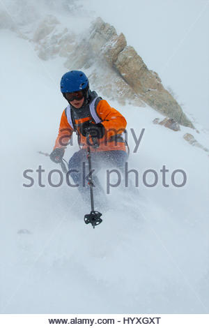 A young teenage boy skis an expert rated steep run off the summit of Allen Peak during full blizzard conditions. - Stock Photo
