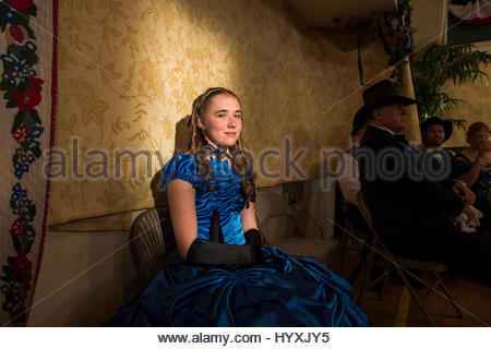 A young woman in period costume watches people dance at the 1864 Grand Victorian Ball for the Montana Territory. - Stock Photo