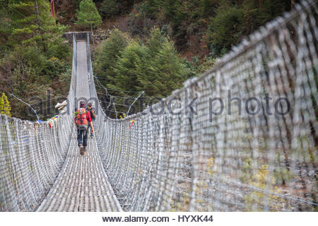 People trekking across a wire mesh footbridge over a river. - Stock Photo