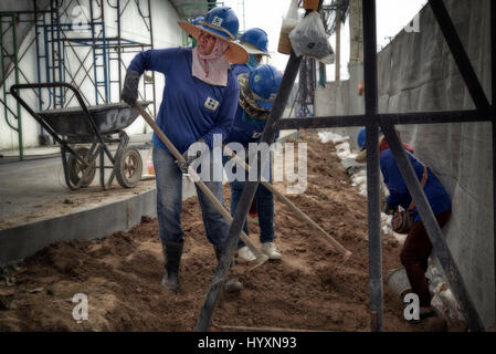 Woman working on a building site. Female builder, construction site, Thailand Southeast Asia - Stock Photo