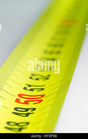 Yellow metal industrial tape measure with standardized metric system such as used in Europe. - Stock Photo
