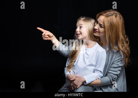 Young mother pointing and showing something to her little daughter on black - Stock Photo