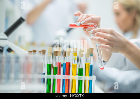 Close-up partial view of female scientist holding test tubes in chemical laboratory - Stock Photo