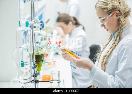 Young female scientist in protective glasses and lab coat looking at test tubes in laboratory - Stock Photo