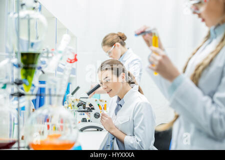 Young female scientist working with microscope while sitting between colleagues in lab - Stock Photo