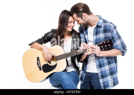 Smiling young couple touching foreheads while playing acoustic guitar - Stock Photo