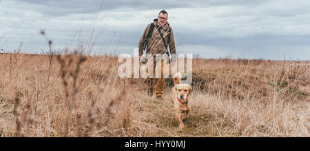 Hiker and small yellow dog walking in grassland on a cloudy day - Stock Photo