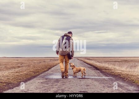 Hiker and dog walking down a road on a cloudy day - Stock Photo