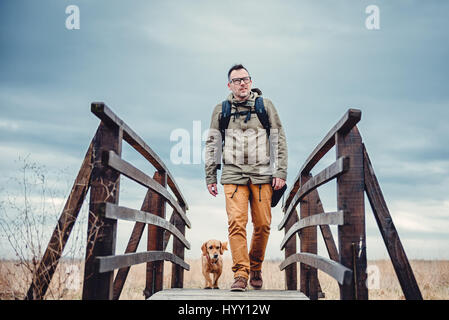 Hiker and dog crossing wooden bridge on the cloudy day - Stock Photo