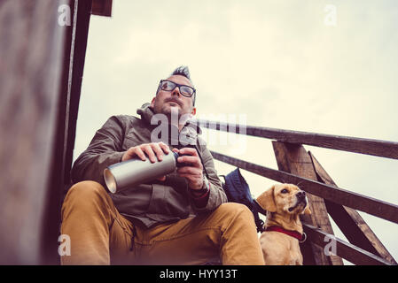 Hiker and dog sitting on the stairs of hikers rest cabin - Stock Photo