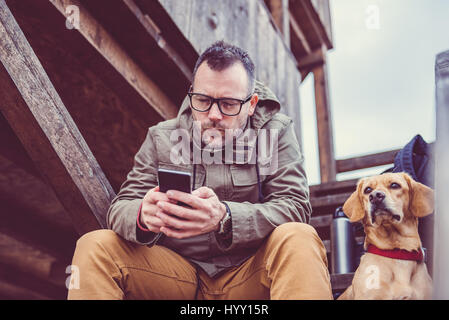 Hiker sitting on the stairs of hikers rest cabin with a dog and using smart phone - Stock Photo