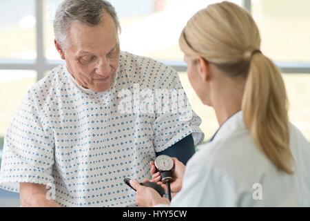 Female doctor taking senior man's blood pressure. - Stock Photo