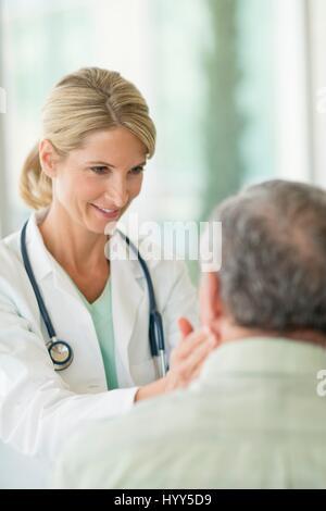 Female doctor touching senior man's neck. - Stock Photo