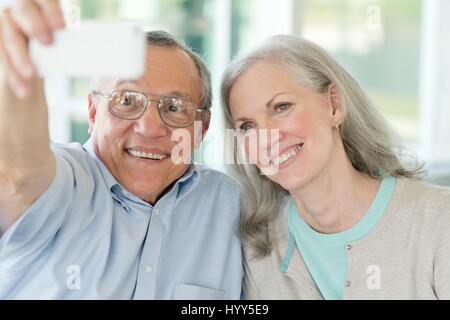 Portrait of senior couple taking selfie on phone. - Stock Photo