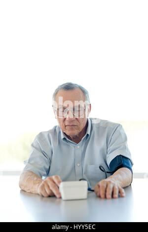 Senior man taking his own blood pressure. - Stock Photo